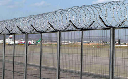 Air port fence with concertina coil razor wire